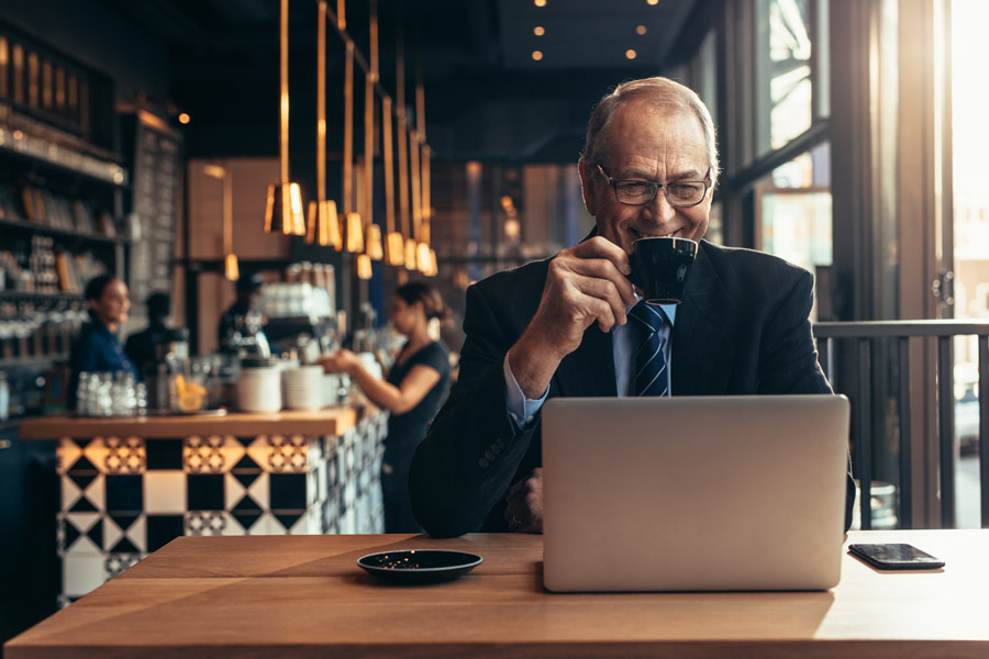 Business Insurance - Man Drinking a Coffee in a Coffee Shop Waiting for a Video Call